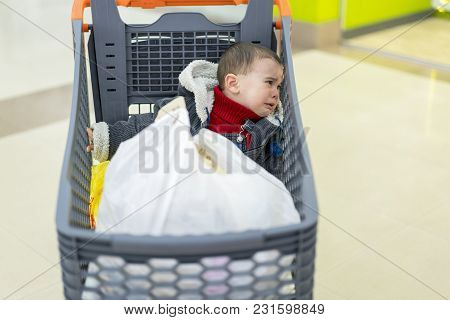 Baby Boy Crying In A Supermarket In A Cart. The Forgotten Child.