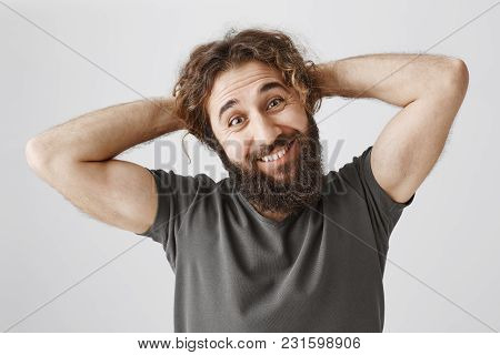 Let Me Scrape Hair In Ponytail. Portrait Of Funny Handsome Arabian Guy With Beard Holding Hands Behi