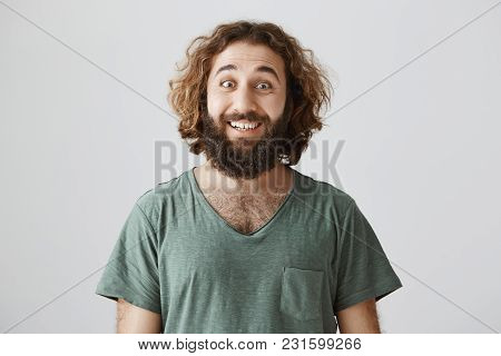 Indoor Shot Of Good-looking Eastern Man With Optimistic Attitude Smiling Broadly And Gazing At Camer