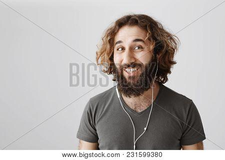 Hiding From Responsibility In Earphones. Studio Shot Of Emotive Handsome Eastern Guy In Earphones Sm