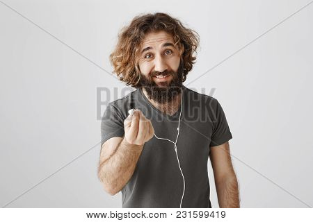 Find Someone Who Will Share Earphones With You. Portrait Of Handsome Friendly Eastern Guy With Curly