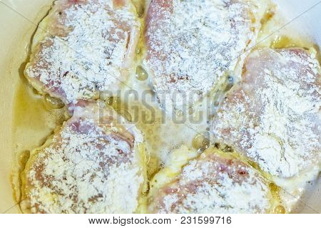 Chicken Thighs In Batter Are Fried In A Frying Pan.