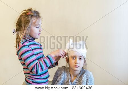Two Girls Play Doctor. Bandage Your Head With A Bandage.