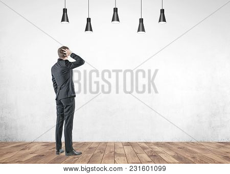 Rear View Of A Confused Businessman Scratching His Head And Thinking. Concept Of Decision Making. A