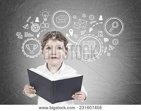 Portrait Of A Cute Little Boy In A White Shirt Holding An Open Book And Looking Upwards. A Blackboar