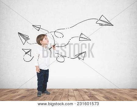 Cute Little Boy In A White Shirt And Dark Jeans Holding A Marker And Looking Upwards. A Concrete Wal