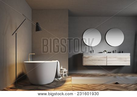 Luxury Bathroom Interior With A Tub, A Double Sink With Two Round Mirrors And A Wooden Floor With A