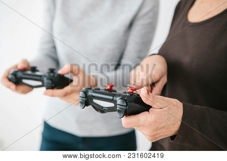 The Elderly Woman Asks The Young Girl How To Use The Joystick For Video Games And Shows Her Finger O