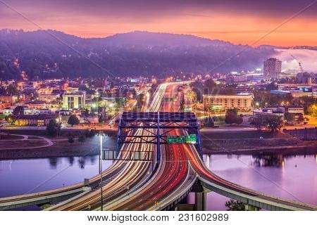 Charleston, West Virginia, USA downtown skyline over the interstate and river.
