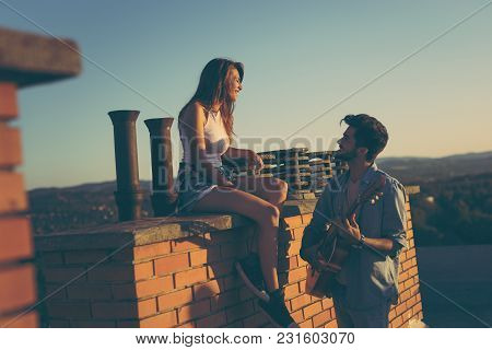 Guy Playing The Guitar To His On A Building Rooftop; Couple At A Summer Rooftop Party Enjoying Sunse