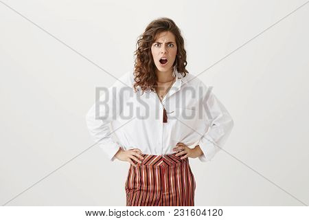 What Are You Looking At. Studio Shot Of Good-looking Woman Standing With Hands On Waist, Frowning An