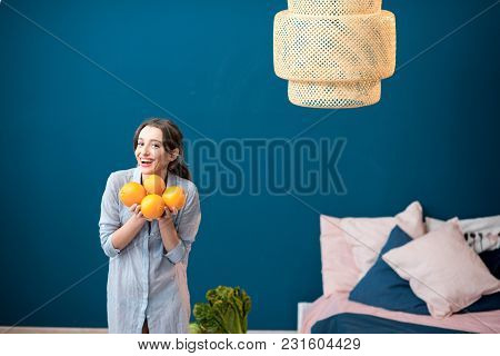 Portrait Of A Young And Happy Woman With Oranges On The Blue Wall Background At Home