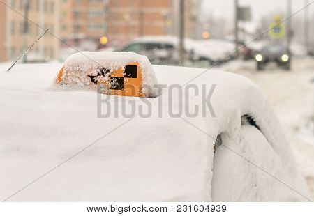 Taxi With A Checkered Car, Snowstorm And Snow In Winter, A Snowdrift On The Roof Parked Waiting For