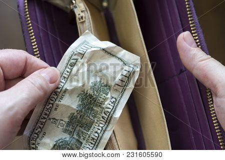 Hand Puts One Hundred Dollar Bill In A Wallet
