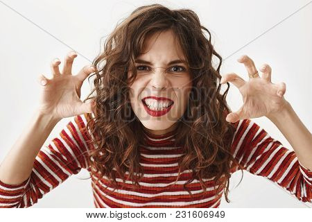 I Will Eat You. Close-up Shot Of Childish Woman Bending Towards Camera With Grimace And Holding Hand