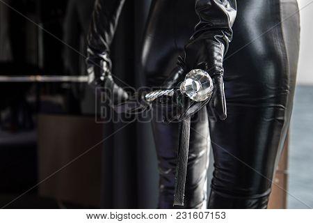 Mistress Holds A Whip Behind Ass. Close-up.