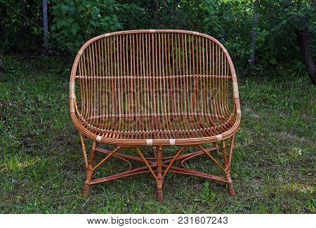 Wicker Armchair On The Background Of A Lawn Of Green Grass