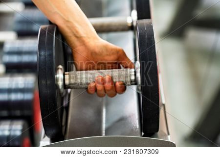 Close Up Hand Of A Sportsperson Grabbing Big Dumbbell In Modern Gym. Healthy Lifestyle Concept