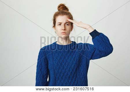 Portrait Of Attractive Serious Female With Red Hair And Freckles Standing In Blue Winter Sweater Sal