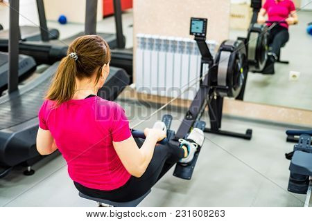 Woman Making Exercises On Rowing Machine In Gym. Back View