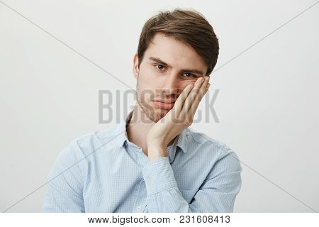 Indoor Shot Of Upset Irritated Caucasian Guy Leaning On Palm And Sighing At Camera, Being Bored And