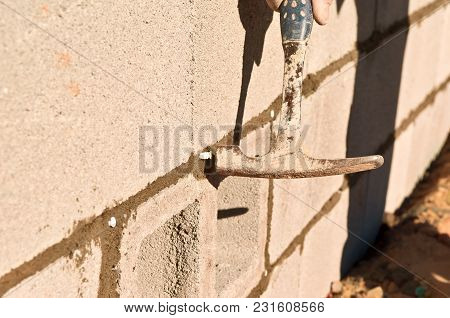 A hammer, captured at the moment of impact, hammering a plastic screw anchor into wet mortar of a newly constructed block wall. poster