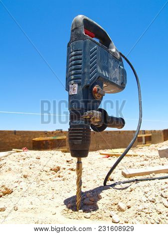 A Drill Left Embedded In The Ground At A Construction Site.
