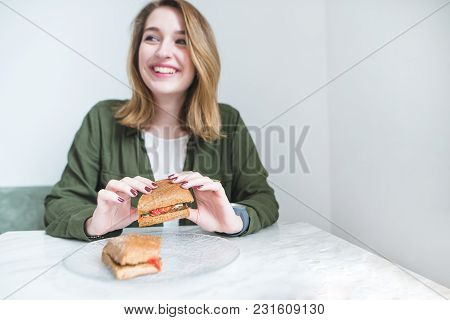 An Appetizing Sandwich In The Hands Of A Smiling Girl Sitting At A Restaurant Table. Positive Girl E