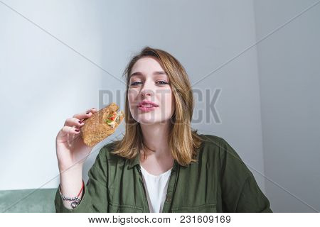 A Pretty Girl With A Sandwich In Her Hands Looks At The Camera And Smiles. The Woman Has Breakfast F