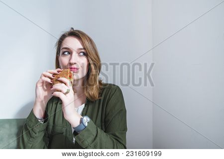 A Cute Girl With A Sandwich In Her Hands Looks To The Side. A Girl Dishes A Sandwich Against A Gray
