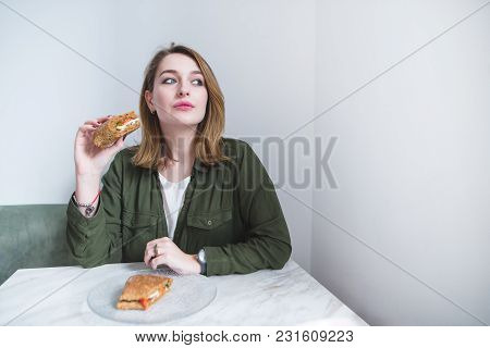 Beautiful Girl Sitting At The Table, Eating A Sandwich And Looking Away. Woman With Sandwich Against