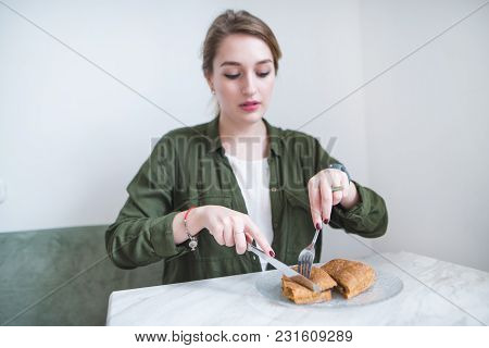 A Beautiful Girl Sits In A Light Restaurant And Eats A Sandwich With A Knife And Fork. The Woman Is