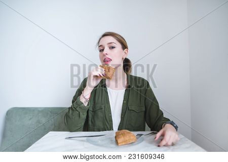A Pretty Woman Licked After Eating A Delicious Sandwich. Woman Sitting At A Table In A Light Restaur