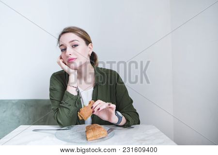 A Sweet Woman Sits In A Restaurant With A Light Interior And Dinner. A Girl With A Sandwich In Her H