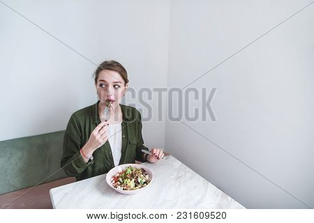 Beautiful Sitting At A Table In A Bright Room And Eating Salad With A Fork. The Girl Bites Green Sal