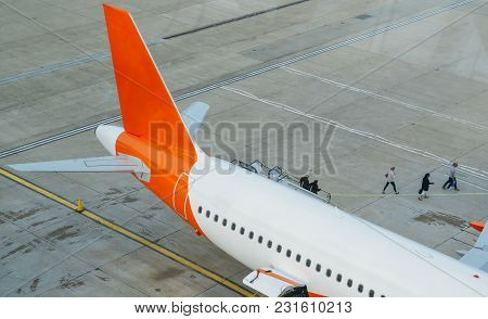 Passengers Disembark From An Airplane And Walk On Tarmac Towards The Terminal Building