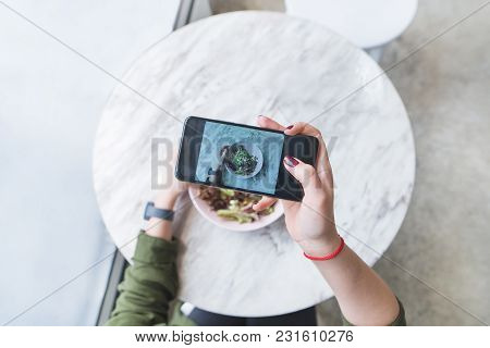 A Woman Makes A Photo Of Her Food At The Restaurant At The Table. The Blogger Picks Up A Salad At Th