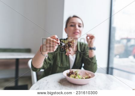A Girl Sits In A Restaurant Near The Window And Directs A Fork With A Salad To The Camera. Green Sal
