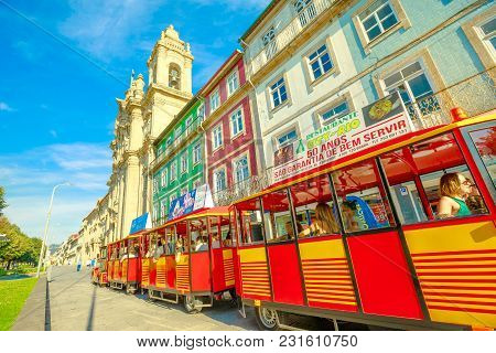 Braga, Portugal - August 12, 2017: Red Tourist Train Along Avenida Central Alongside Convent Of Cong