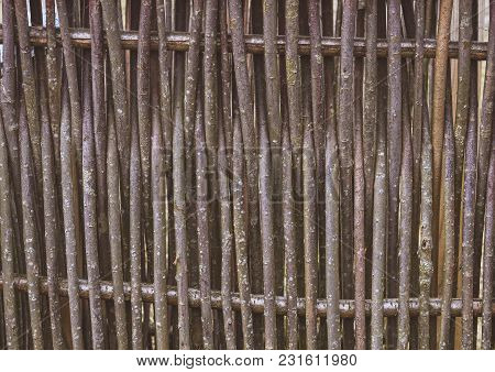 A Woven Wooden Fence Made Of Thin Old Branches In The Countryside In Vintage Style.