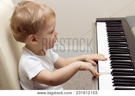 Cute Blond Two Years Toddler Playing On The Electronic Piano.