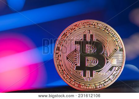 Golden Bitcoin On Neon Lit Purple And Blue Background