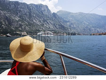 Woman In A Wide-brimmed Straw Hat Sits In Boat And Looks At The Sea And Mountains. Back View. Monten