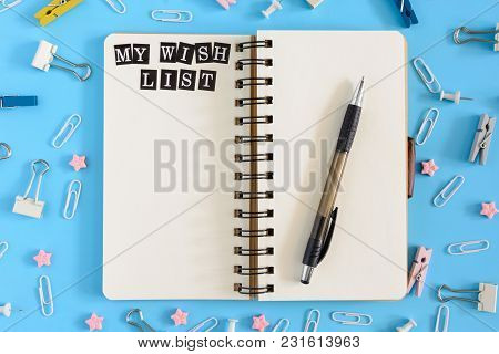 Stationery In Disorder On A Blue Background. In The Center Lies An Open Notebook On Springs With Whi