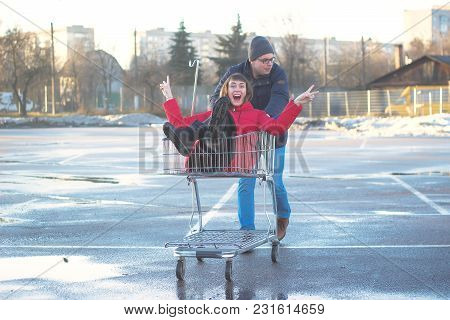 Two Happy Man And Woman Having Fun With Shopping Cart Outdoors