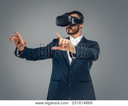 Bearded Male Dressed In A Suit With Virtual Reality Glasses On His Head.