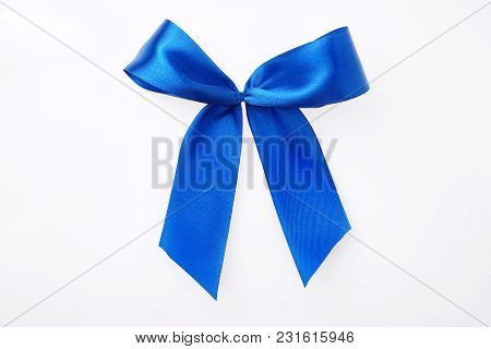 Textile Ribbon Tied In Bow. Cobalt Blue Satin. Isolated On White. Close Up. Gift Concept. Top View.