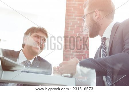 View from below of two businessmen working on his laptop