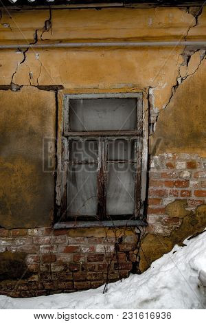 Shabby Grungy Cracked Wall, Broken Windows, Abandoned House, Winter, Poverty Concept.