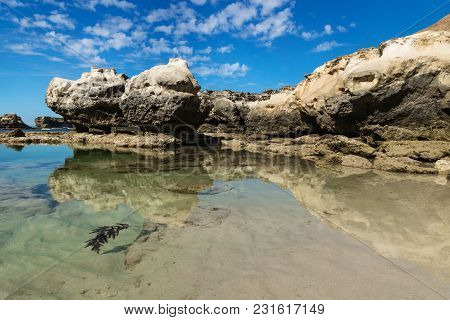Rock Formation With Clliff With Reflections In The Sea At Peterborough Beach Along The Great Ocean R